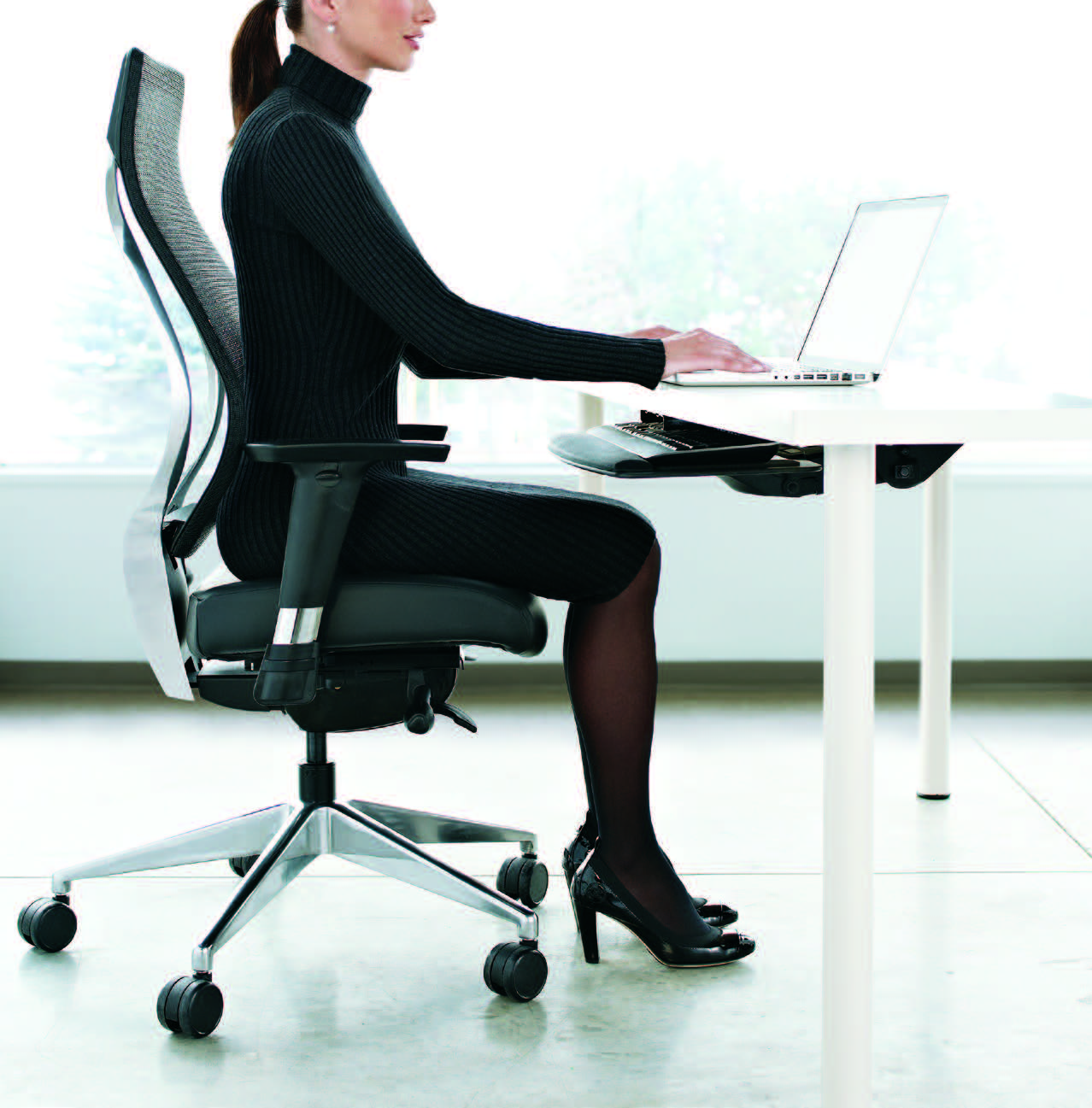 woman sitting on a polished aluminum you task chair working at her desk