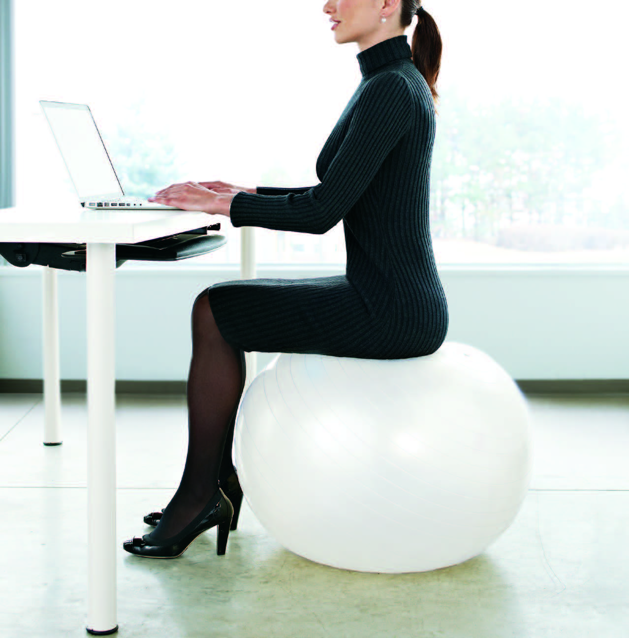 woman sitting on a white yoga ball working at her desk